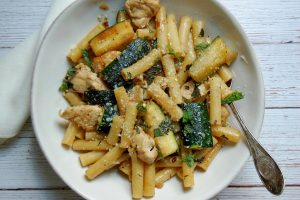 bowl of ziti pasta with zuchini, chicken, onion, and mint in white bowl