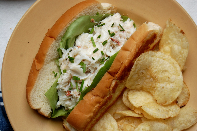 crab roll in bun with potato chips on plate