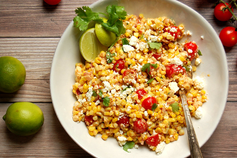 bowl of mexican street corn salad with tomatoes cotija lime