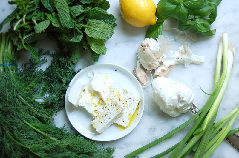 greek goddess dip ingredients feta garlic fresh herbs lemon on marble