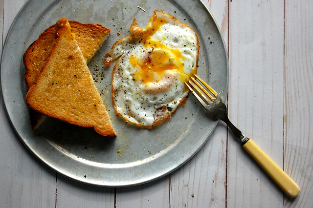 fried egg and buttered toast on metal plate with fork