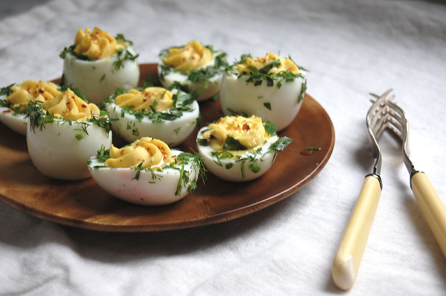 Deviled Eggs With Herbs on wooden dish with forks
