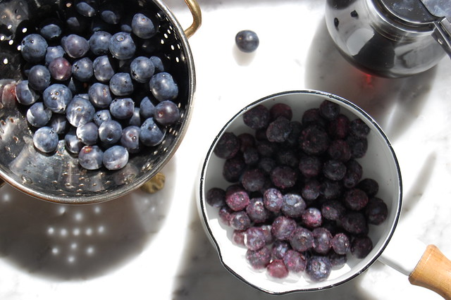 fresh blueberries in colander and pot with maple syrup