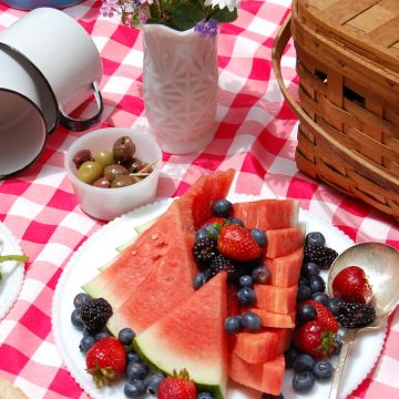 picnic spread of basket watermelon olives, and salad