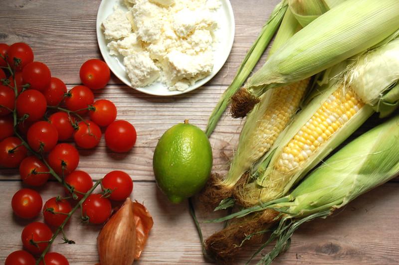 corn salad ingredients tomatoes lime corn cotija on wood