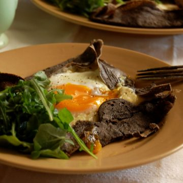 ham egg and cheese buckwheat galette on plate with salad