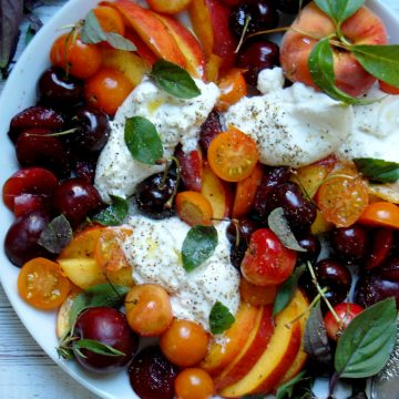 white platter of burrata and stone fruit caprese with basil peaches cherries
