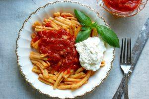 bowl of pasta with marinara sauce and ricotta and basil