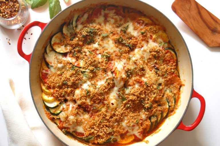 cooked zucchini and yellow squash parmesan parmigiana in red casserole with breadcrumbs and cheese