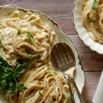 serving platter of fettuccini alfredo e pepe with parsley on wooden table