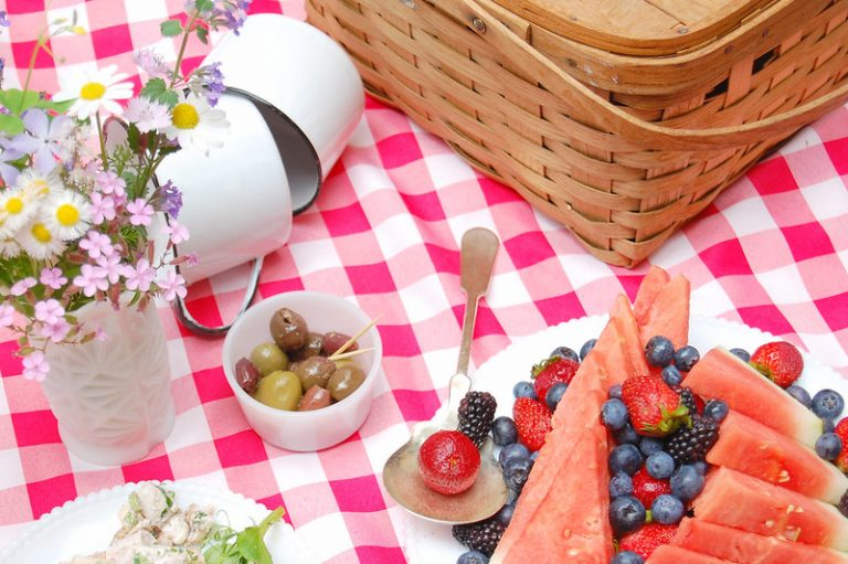 picnic spread with fruit, salad, olives, and picnic basket