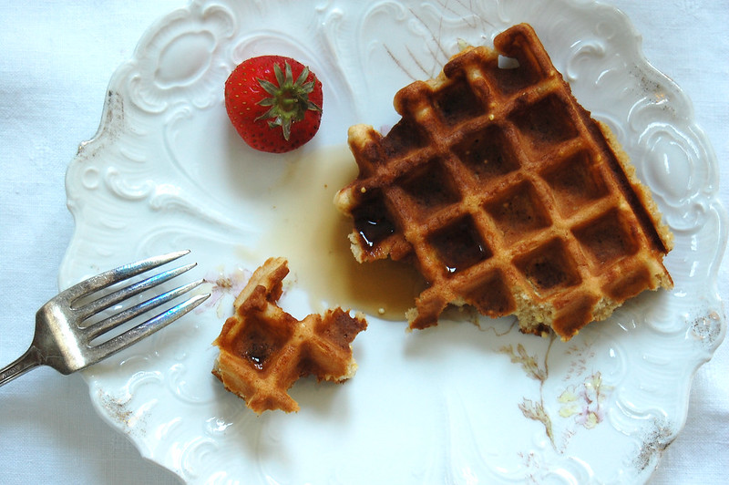 partially eaten waffle with syrup on while plate