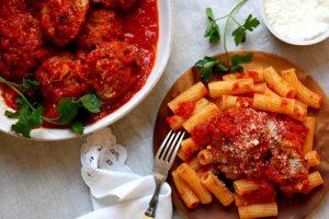 bowl of italian meatballs in tomato sauce with rigatoni pasta