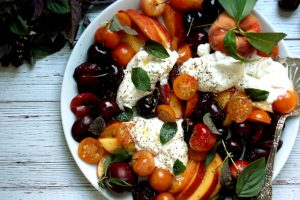 platter of burrata with grape tomatoes cherries and stone fruits