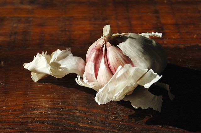 peeled garlic bulb on wood