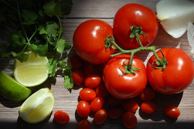 tomatoes lime cilantro salsa onion on wood