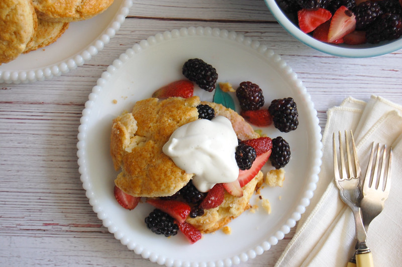 berry biscuits on white plate topped with vanilla whipped cream