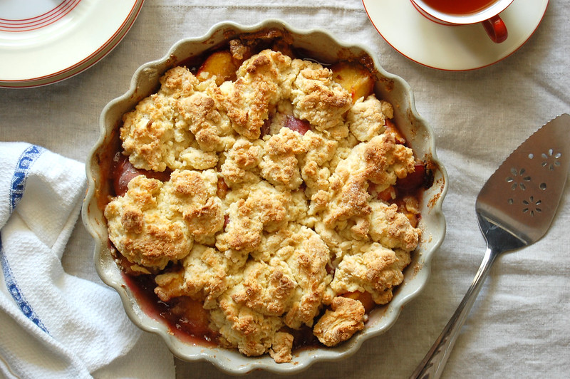 baked unpeeled peach cobbler with biscuit topping on linen