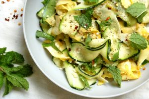 bowl of zucchini ribbon salad with mint and parmesan cheese with grater