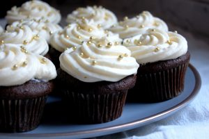 platter of chocolate cupcakes with vanilla buttercream frosting with gold decoration
