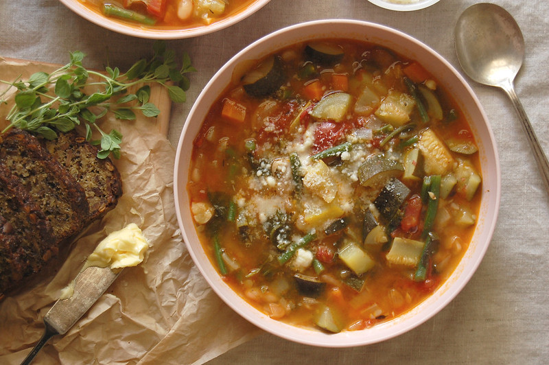 bowl of tomato zucchini minestrone soup in pink bowl
