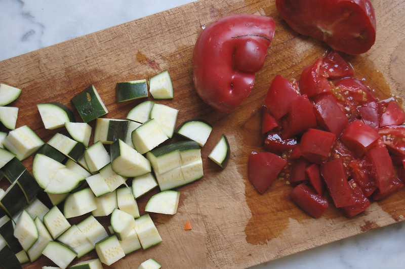 diced zucchini and tomatoes on wooden board for minestrone