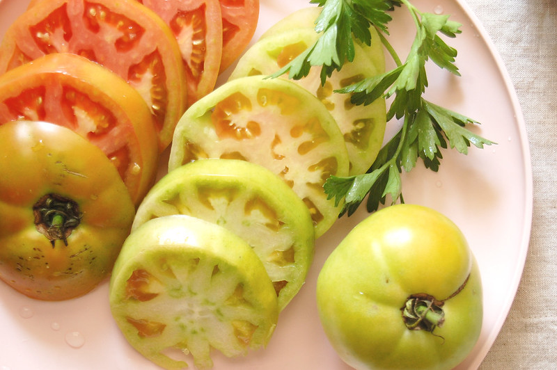 sliced pink and green tomatoes on pink plate with parsley