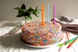 birthday funfetti sprinkle cake on table with candles and cake server