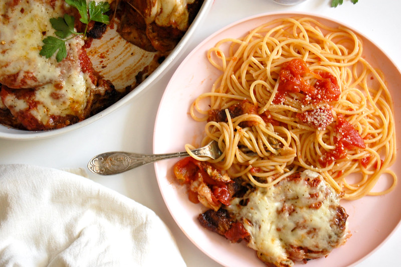 slice of eggplant parmesan on plate with spaghetti and fork