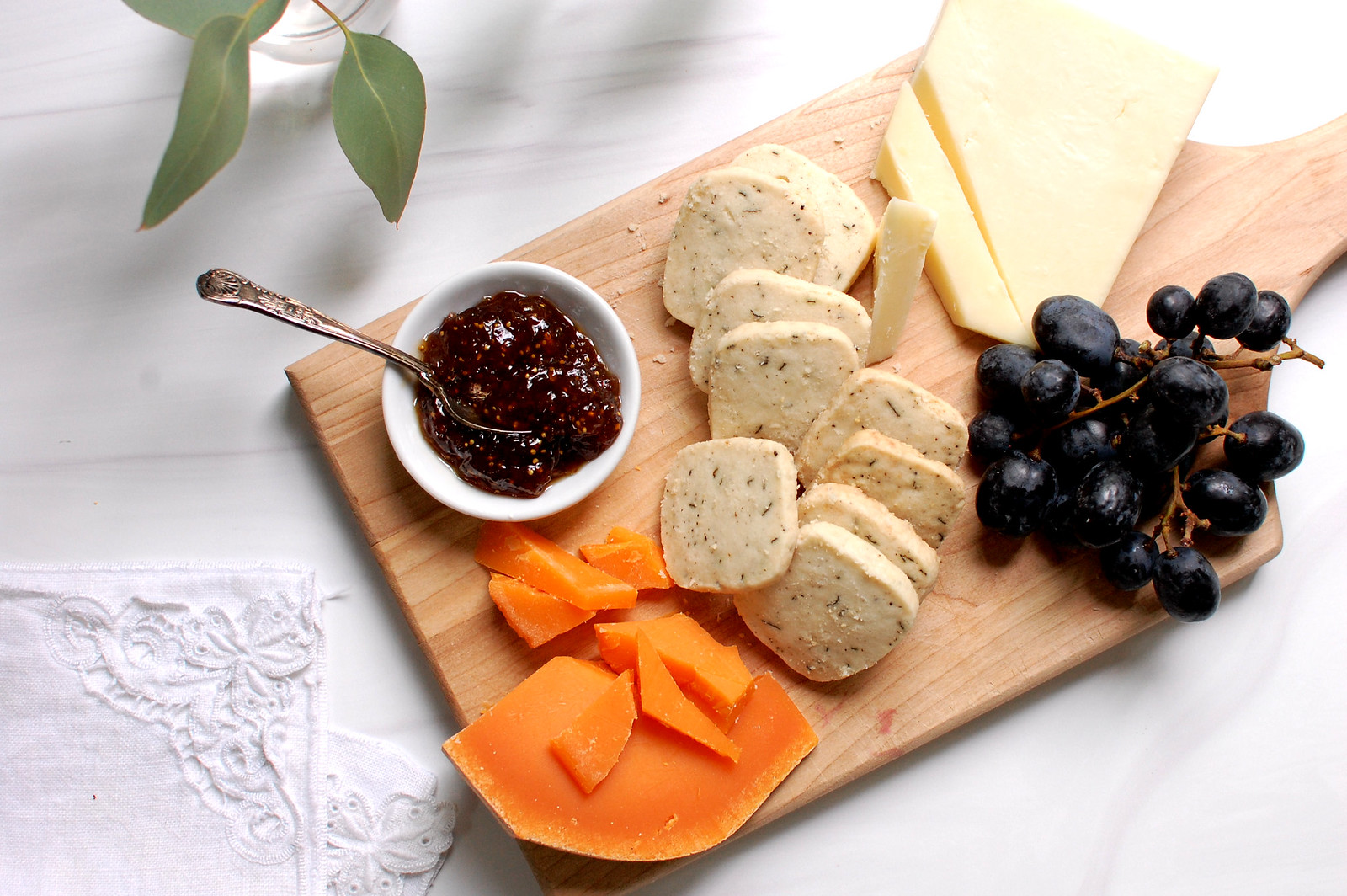 wood cutting board with cheese and crackers