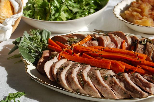 platter of sliced pork tenderloin with applesauce and salad