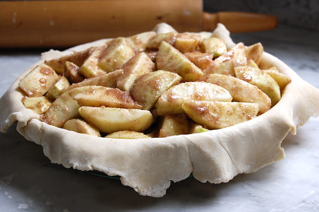 sliced apples in raw apple pie dough shell