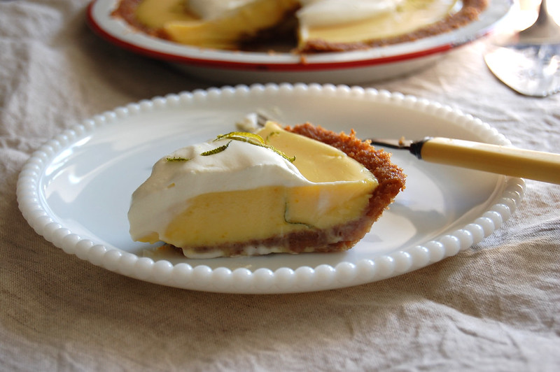 slice of key lime pie with whipped cream and zest on white dish