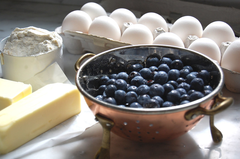 colander of fresh blueberries with eggs and butter for best blueberry muffin recipe
