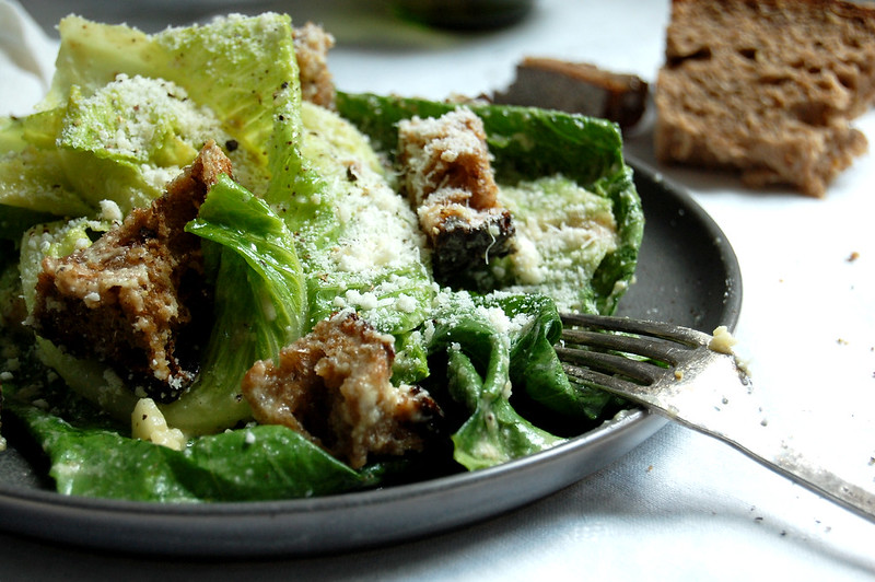 caesar salad on gray plate with fork an big croutons
