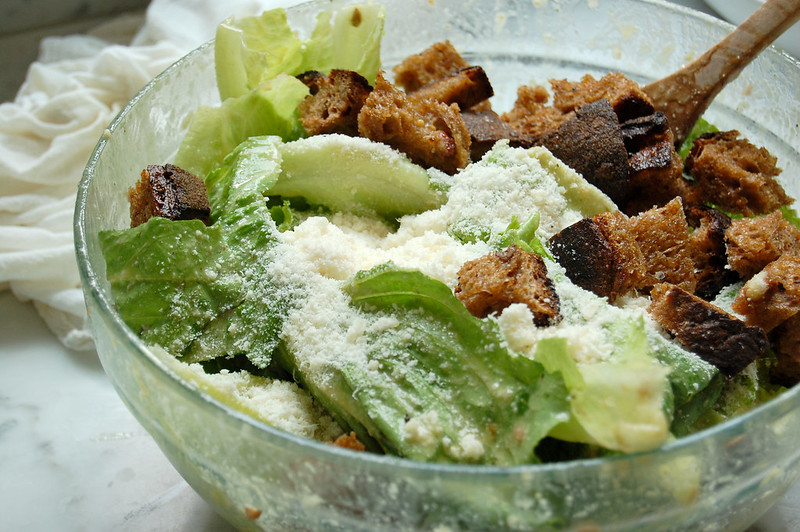caesar salad ingredients getting mixed in bowl cheese, croutons, romaine lettuce, anchovies