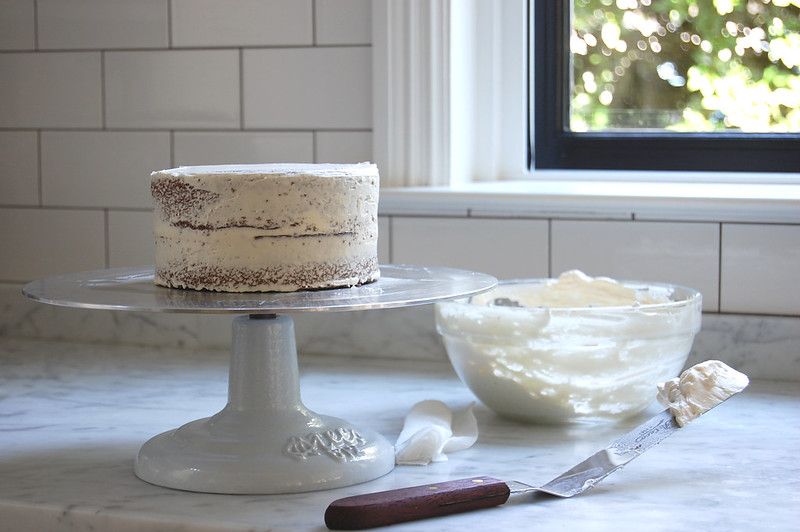 cake covered with buttercream frosting on cake stand