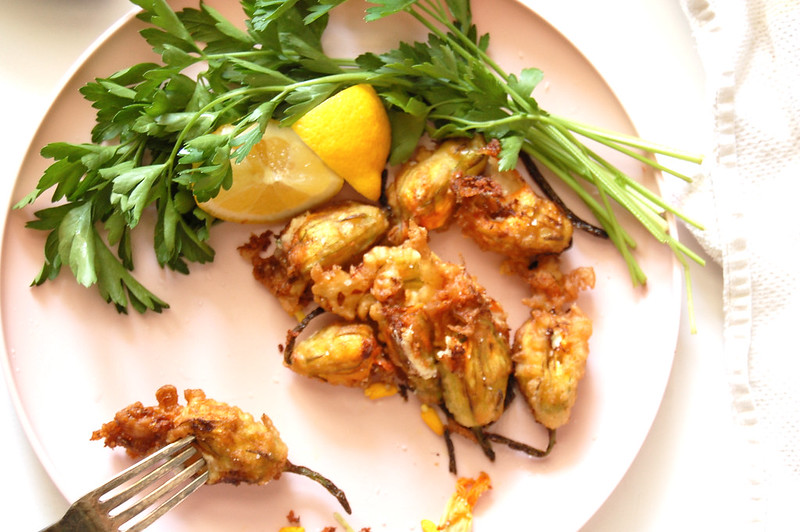 pink dish of fried stuffed squash blossoms with lemon and parsley