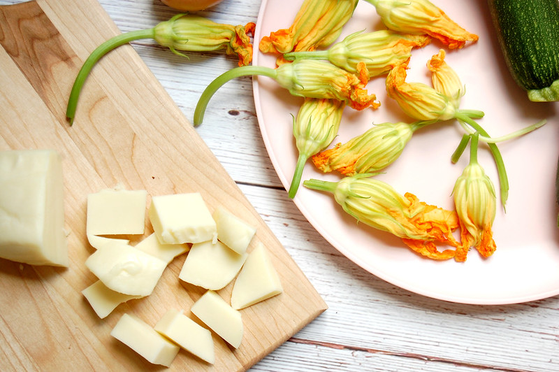 zucchini squash blossoms with cheese on wooden board