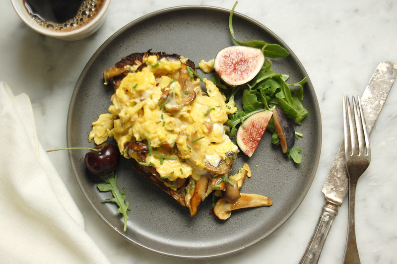 gray plate with finished scrambled eggs with mushrooms and figs with coffee