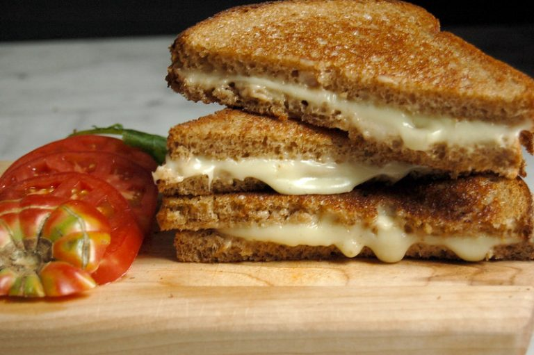 stack of melted grilled cheese sandwiches with sliced tomato on wooden board