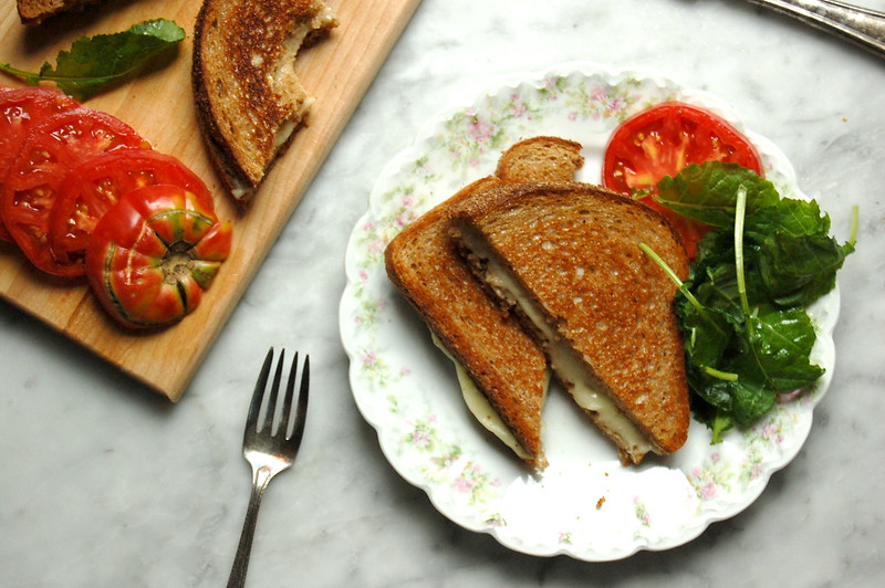 best grilled cheese sandwich recipe on plate with tomatoes and cutting board