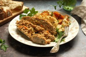 plate of sliced turkey meatloaf with root vegetables and bread