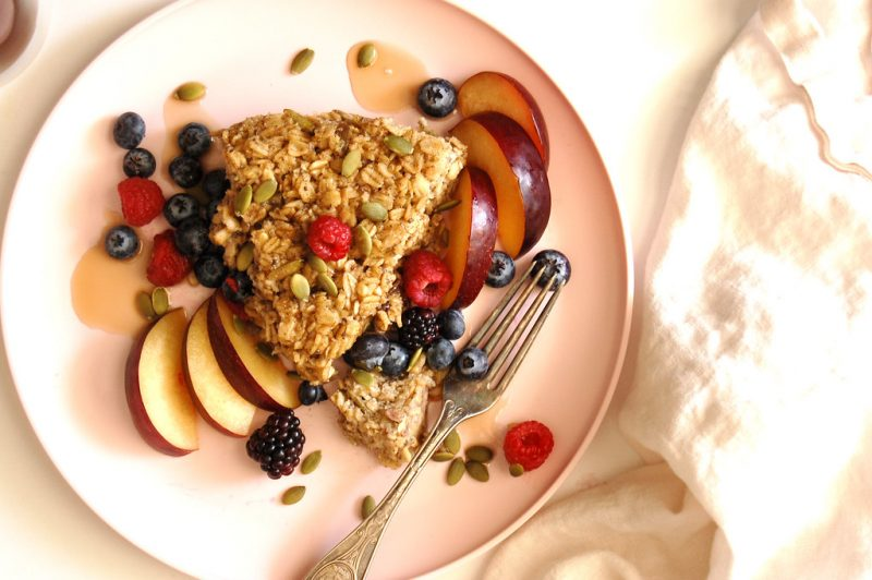 slice of healthy baked oatmeal on plate with berries and maple syrup