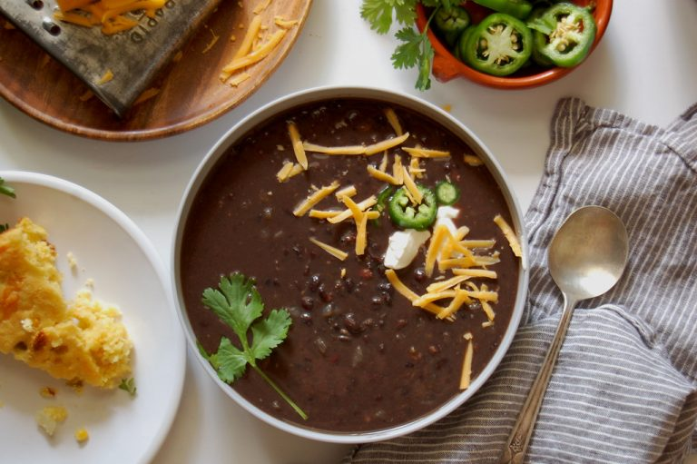 bowl of black bean soup with cheddar cilantro jalepeno with spoon