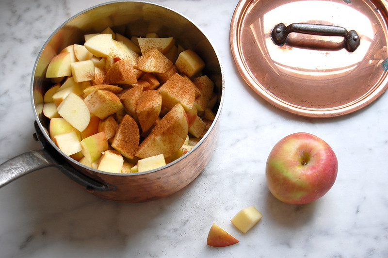 copper pot with diced apples and cinnamon for applesauce
