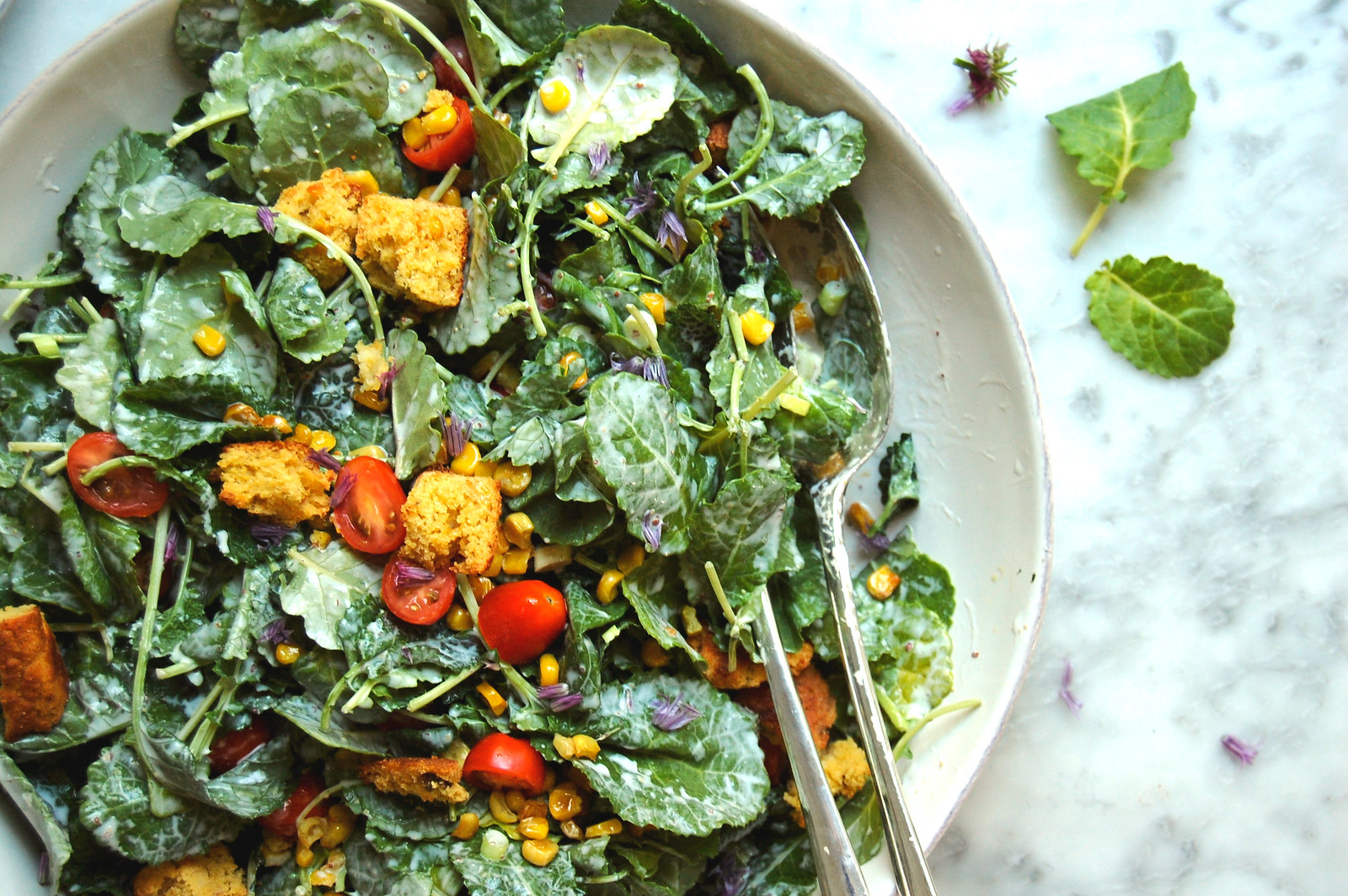 kale salad with corn and tomatoes and croutons