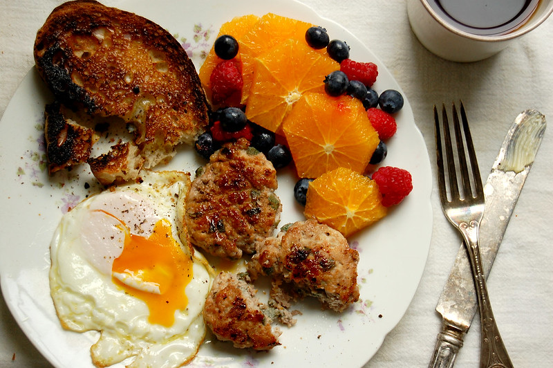 maple sage breakfast sausage on plate with eggs toast and fresh fruit breakfast plate