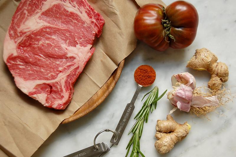 beef tibs recipe raw steak, spices, ginger, onion, garlic tomato