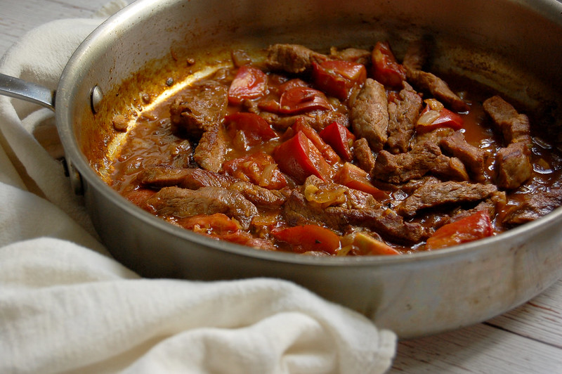 cooked beef tibs stewed in tomato in skillet